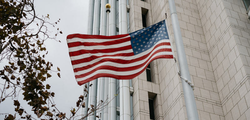 American flag with a skyscraper in the background.