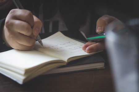 Close up of man on his smartphone while writing in a notebook.