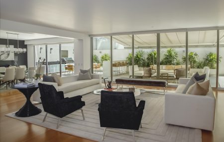 Living room and kitchen in a home with large windows and modern, sophisticated decor. as part of a virtual home tour.