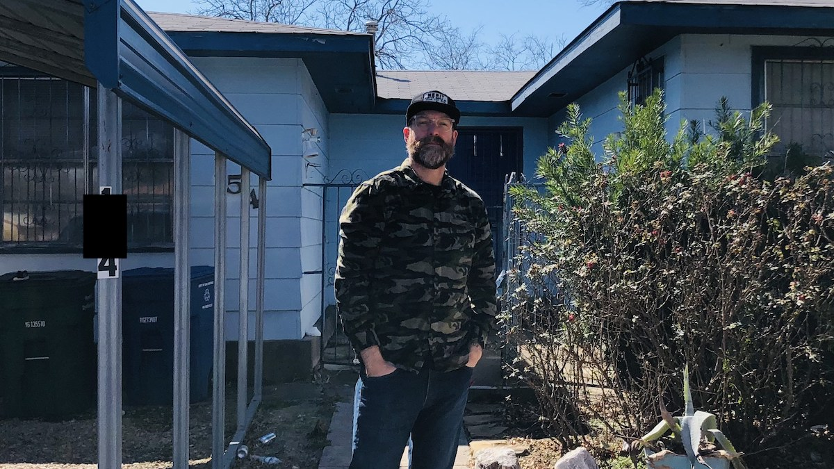An image of a bearded man in a long shirt standing in front of a house. This MyHouseDeals member spoke about how to invest in a rental property and using the process as al learning experience.