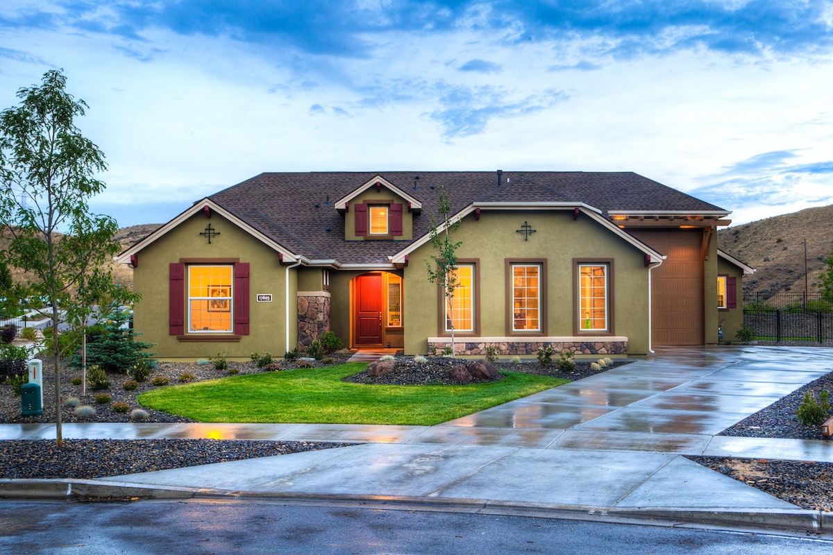 This is a picture of a house with five windows, one on the left of the front door, three on the right of the front door. There's one window above the front door as well. The lawn is relatively simple. Keep lawns fairly neutral, as buyers may want to personalize them.