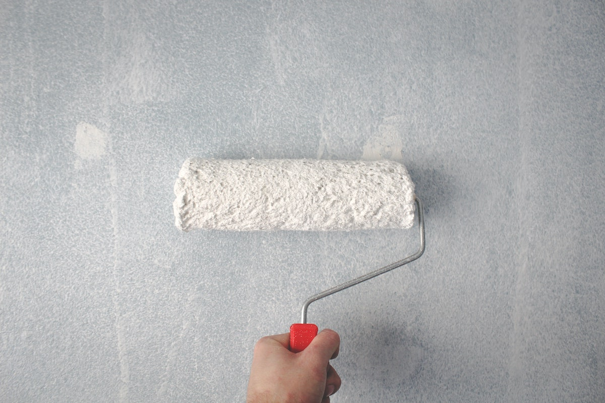 ARV in real estate can be boosted by painting the house. This is a picture of a person holding a paint roller against a wall.
